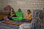 In this Tuesday, Feb. 11, 2020 photo, from left, daughter Zeel, wife Niruben, and son Bhavin sit mourning the death of Bhalabhai Makwana, one of the victims of Saturday's fire at a Nandan Denim garment factory in Ahmedabad, India. At least seven people died when a blaze swept the garment factory that has ties to major U.S. retailers, according to its website. Some of the U.S. and multinational companies listed on the website said they were not actually customers, and many issued statements that strongly condemned dangerous work sites. (AP Photo/Ajit Solanki)