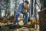 In this March 24, 2019, photo, Gene Mapa collects metal and ceramic objects that didn't burn in the Camp Fire at his house in Paradise, Calif. Mapa now lives in Colfax, which as a similar level of fire risk. A former supply hub for gold mining camps, Colfax sits a few miles from the edge of the Tahoe National Forest in the lower-elevation Sierra. It straddles Interstate 80 and serves as the last major stop between the Sacramento metropolitan area and the Lake Tahoe region. Horses graze beside deer on large ranchettes in the rugged brushy canyons along the outskirts of the city. (Hector Amezcua/The Sacramento Bee via AP)