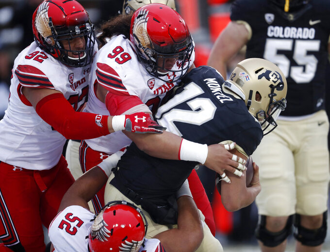 FILE - In this Nov. 17, 2018, file photo, Colorado quarterback Steven Montez (12) is sacked by Utah defensive tackle John Penisini (99), defensive end Maxs Tupai (92) and defensive tackle Leki Fotu (52) during the second half of an NCAA college football game in Boulder, Colo. Utah plays Washington in the Pac-12 championship game. Utah leads the Pac-12 with 8.2 tackles for loss per game, which plays a big role in holding opposing offenses to a league-best 33.2 percent conversion rate on third down when they are able to bring even more pressure on the quarterback. (AP Photo/David Zalubowski, File)