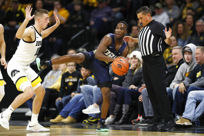 Oral Roberts guard R.J. Fuqua, center, passes around Iowa guard Joe Wieskamp, left, during the first half of an NCAA college basketball game, Friday, Nov. 15, 2019, in Iowa City, Iowa. (AP Photo/Charlie Neibergall)