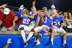 SMU cornerback Justin Guy-Robinson (29), place kicker Kevin Miles (93) and safety Brice Madison (34) celebrate with fans after a 37-20 victory over Tulane in an NCAA football game at Ford Stadium on Saturday, Nov. 30, 2019, in Dallas. (Smiley N. Pool/The Dallas Morning News via AP)