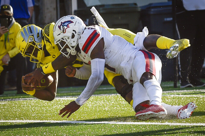 Oregon quarterback Anthony Brown (13) scores as he is hit by Stony Brook defensive back Carthell Flowers (17) during the second quarter of an NCAA college football game Saturday, Sept. 18, 2021, in Eugene, Ore. (AP Photo/Andy Nelson)