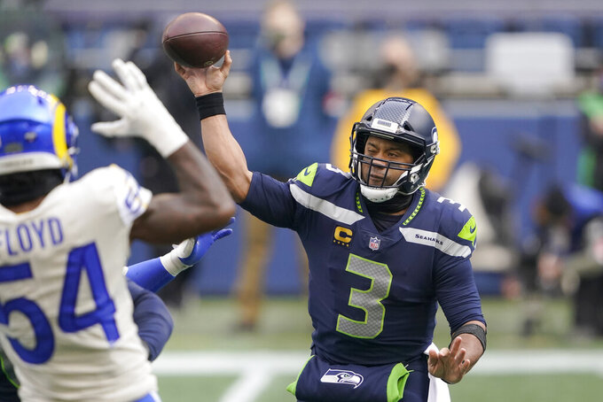Seattle Seahawks quarterback Russell Wilson (3) throws as Los Angeles Rams outside linebacker Leonard Floyd defends during the first half of an NFL wild-card playoff football game, Saturday, Jan. 9, 2021, in Seattle. (AP Photo/Ted S. Warren)