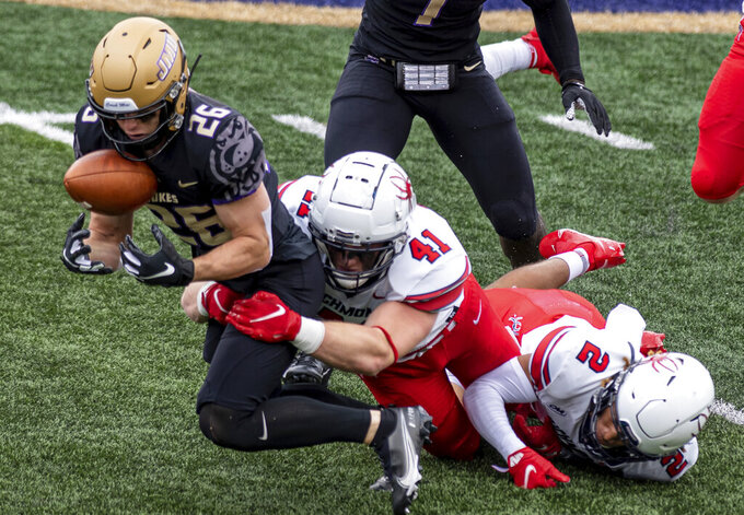James Madison cornerback Jack Sroba (26) tries to hang onto the ball as he gets tackled by Richmond linebacker Tyler Dressler (41) during the first half of an NCAA college football game in Harrisonburg, Va., Saturday, April 17, 2021. (Daniel Lin/Daily News-Record Via AP)