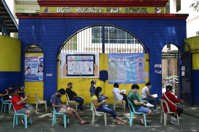 People wearing masks and face shields wait for their turn to pick up student electronic tablets as online classes are scheduled to start next week in the Dona Rosario High School in Quezon city, Philippines, Thursday, Oct. 1, 2020. Public schools will hold online classes using electronic gadgets and educational materials provided to students as the opening got delayed due to the coronavirus pandemic. (AP Photo/Aaron Favila)