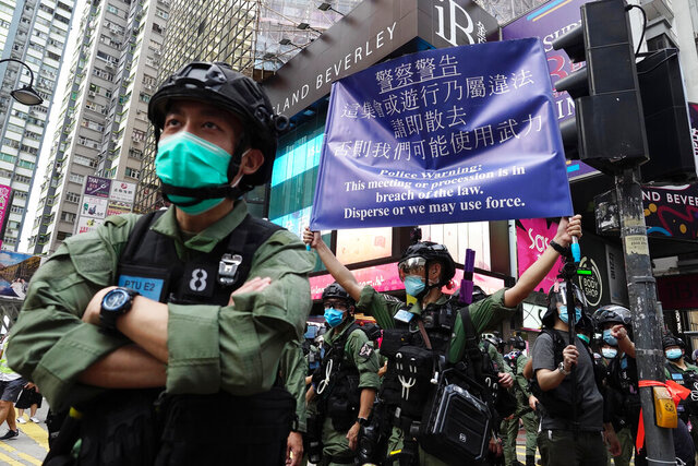 A police officer displays a warning banner on China's National Day in Causeway Bay, Hong Kong, Thursday, Oct. 1, 2020. A popular shopping district in Causeway Bay saw a heavy police presence on the National Day holiday despite low protester turnout. (AP Photo/Vincent Yu)