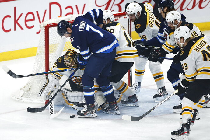 Boston Bruins goaltender Tuukka Rask (40) keeps Winnipeg Jets' Dmitry Kulikov (7) away from the puck during the first period of an NHL hockey game Friday, Jan. 31, 2020, in Winnipeg, Manitoba. (John Woods/The Canadian Press via AP)