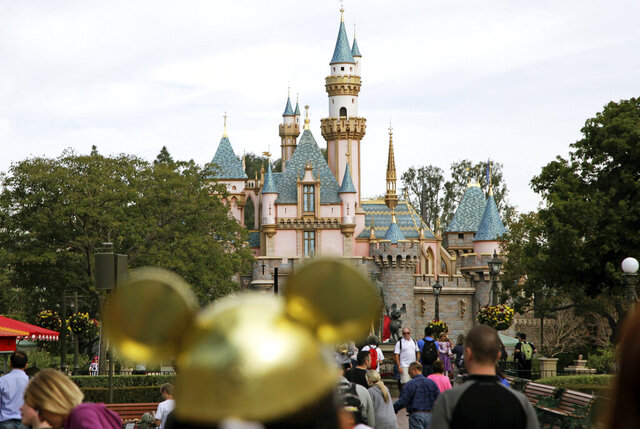 FILE - In this Jan. 22, 2015, file photo, visitors walk toward Sleeping Beauty's Castle in the background at Disneyland Resort in Anaheim, Calif.  Saying they don't know when they'll be able to re-open many of their businesses with the coronavirus spreading, Walt Disney Co. officials announced they will start furloughing workers in two weeks at its theme parks resorts in Florida and California. The statement released late Thursday, April 2, 2020  from The Walt Disney Co. said the first wave of furloughs will start April 19 and involve workers whose jobs aren't necessary at this time.  (AP Photo/Jae C. Hong, File)