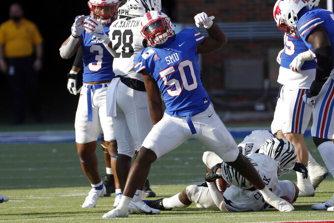 SMU linebacker Richard McBryde (50) celebrates a tackle of Memphis running back Rodrigues Clark, bottom right, during the second half of an NCAA college football game in Dallas, Saturday, Oct. 3, 2020. (AP Photo/Roger Steinman)