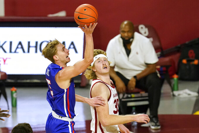 Houston Baptist guard Hunter Janacek (5) shoots in front of Oklahoma forward Brady Manek (35) in the first half of an NCAA college basketball game Saturday, Dec. 19, 2020, in Norman, Okla. (AP Photo/Sue Ogrocki)