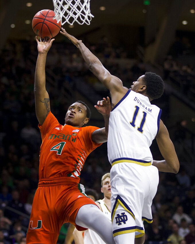 Miami's Keith Stone (4) goes up for a shot as Notre Dame's Juwan Durham (11) defends during the first half of an NCAA college basketball game Sunday, Feb. 23, 2020, in South Bend, Ind. (AP Photo/Robert Franklin)