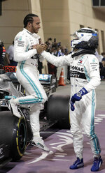 Mercedes driver Lewis Hamilton of Britain, left, is helped down from his car by Mercedes driver Valtteri Bottas of Finland after winning the Bahrain Formula One Grand Prix at the Bahrain International Circuit in Sakhir, Bahrain, Sunday, March 31, 2019. (AP Photo/Hassan Ammar)