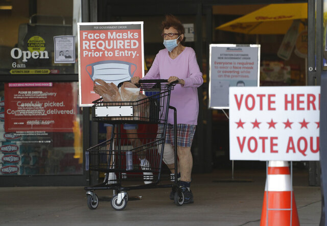 A shopper wearing a mask for protection against COVID-19 leaves a grocery store that is also searing as an early polling site, Thursday, July 9, 2020, in Austin, Texas. (AP Photo/Eric Gay)