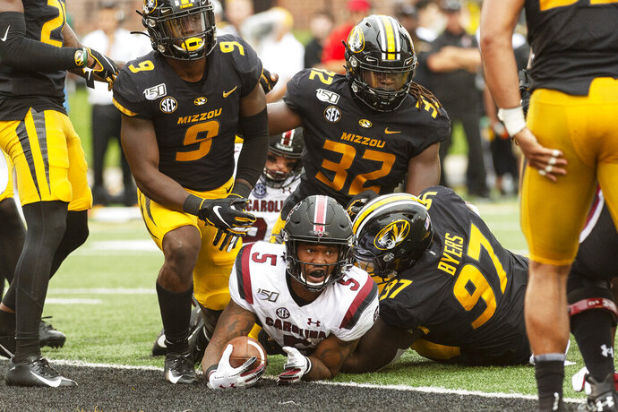 South Carolina running back Rico Dowdle, bottom, looks up after he scored a touchdown past Missouri's Tyree Gillespie, left, Akial Byers, right, and Nick Bolton, top, during the second quarter of an NCAA college football game, Saturday, Sept. 21, 2019, in Columbia, Mo. (AP Photo/L.G. Patterson)