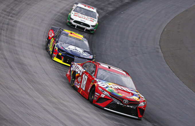 Kyle Busch (18) leads Kyle Busch (24) and Kevin Harvick (4) through a turn during a NASCAR Cup Series auto race, Sunday, April 7, 2019, in Bristol, Tenn. (AP Photo/Wade Payne)