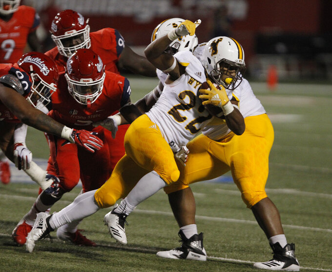 Wyoming running back Nico Evans runs past Fresno State defensive tackle Kevin Atkins, left, and defensive end Mykal Walker (3) during the first half of an NCAA college football game in Fresno, Calif., Saturday, Oct. 13, 2018. (AP Photo/Gary Kazanjian)