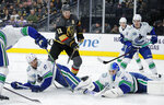 Vancouver Canucks goaltender Jacob Markstrom (25) covers the puck against Vegas Golden Knights right wing Mark Stone (61) during the second period of an NHL hockey game Sunday, Dec. 15, 2019, in Las Vegas. (AP Photo/John Locher)
