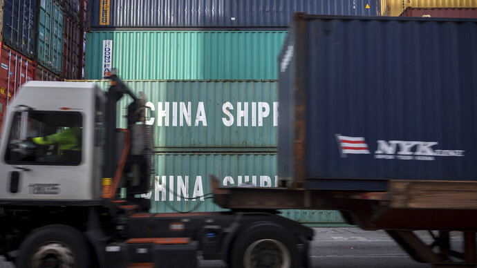 In this Thursday, July, 5, 2018 photo, a jockey truck passes a stack of 40-foot China Shipping containers at the Port of Savannah in Savannah, Ga. The United States and China launched what Beijing called the
