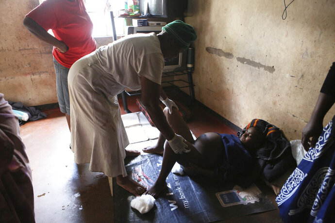 72-year old grandmother Esther Zinyoro Gwena, left, attends to a woman in labor in her tiny apartment in the poor surburb of Mbare in Harare, Zimbabwe, Saturday, Nov. 16, 2019. Grandmother Esther Zinyoro Gwena claims to be guided by the holy spirit and has become a local hero, as the country's economic crisis forces closure of medical facilities, and mothers-to-be seek out untrained birth attendants. (AP Photo/Tsvangirayi Mukwazhi)