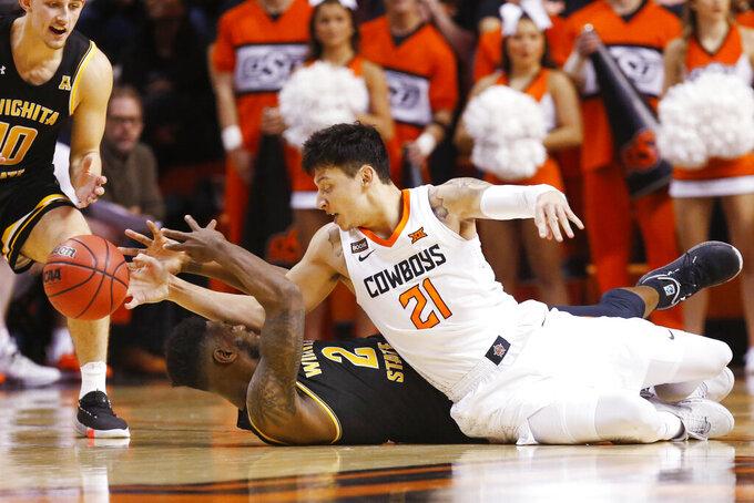 Oklahoma State guard Lindy Waters III (21) knocks the ball away from Wichita State guard Jamarius Burton (2) in the second half of an NCAA college basketball game in Stillwater, Okla., Sunday, Dec. 8, 2019. (AP Photo/Sue Ogrocki)