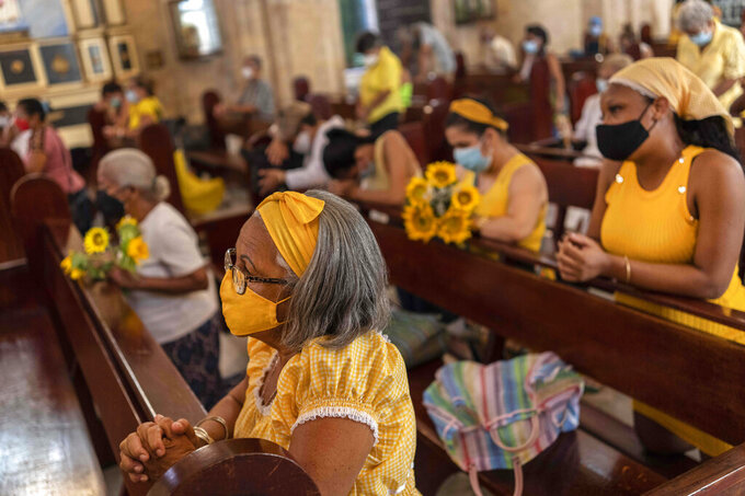People wearing masks amid the COVID-19 pandemic kneel during Mass at Our Lady of Cobre Church on the feast day of Cuba's patron saint, the Virgin of Charity of Cobre, in Havana, Cuba, Wednesday, Sept. 8, 2021. For the second year in a row, the annual procession with the statue of the Virgin of Charity of Cobre was cancelled due to the pandemic. (AP Photo/Ramon Espinosa)
