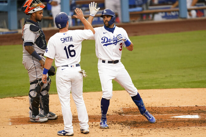 Los Angeles Dodgers' Chris Taylor, right, high-fives Will Smith after Taylor hit a home run during the second inning of the team's baseball game against the Houston Astros at Dodger Stadium on Saturday, Sept. 12, 2020, in Los Angeles. (AP Photo/Ashley Landis)