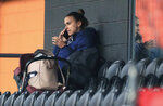 Tottenham Hotspur women's Alex Morgan speaks on her phone in the stands, during the women's Continental League Cup match between Tottenham Hotspur and London City Lionesses , at the Hive Stadium, in London, Wednesday, Oct. 7, 2020. (Mike Egerton/PA via AP)