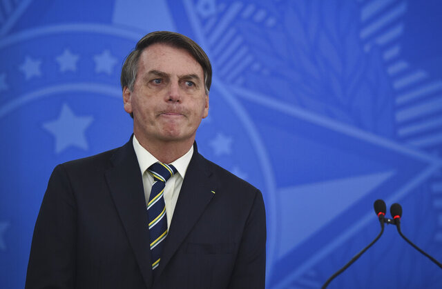 Brazil's President Jair Bolsonaro speaks to journalists about the new coronavirus at Planalto presidential palace in Brasilia, Brazil, Friday, March 27, 2020. Even as coronavirus cases mount in Latin America's largest nation, Bolsonaro is calling the pandemic a momentary, minor problem and saying strong measures to contain it are unnecessary. (AP Photo/Andre Borges)