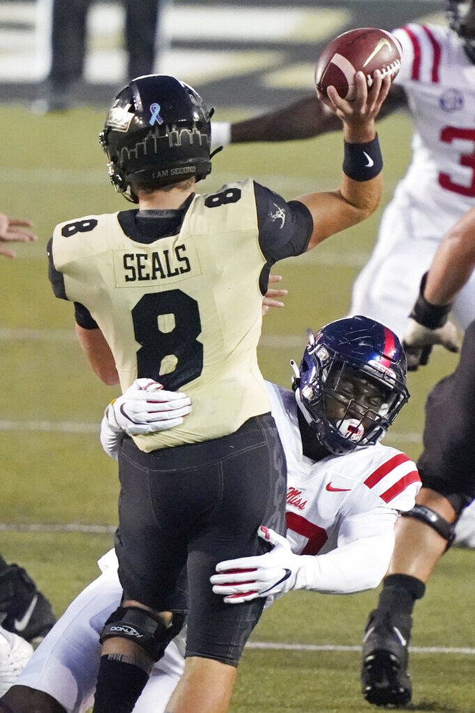 Vanderbilt quarterback Ken Seals (8) gets a pass away as he is hit by Mississippi linebacker Cedric Johnson in the second half of an NCAA college football game Saturday, Oct. 31, 2020, in Nashville, Tenn. Mississippi won 54-21. (AP Photo/Mark Humphrey)
