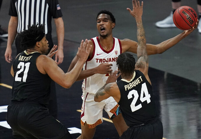 Southern California's Evan Mobley (4) passes around Colorado's Evan Battey (21) and Eli Parquet (24) during the first half of an NCAA college basketball game in the semifinal round of the Pac-12 men's tournament Friday, March 12, 2021, in Las Vegas. (AP Photo/John Locher)