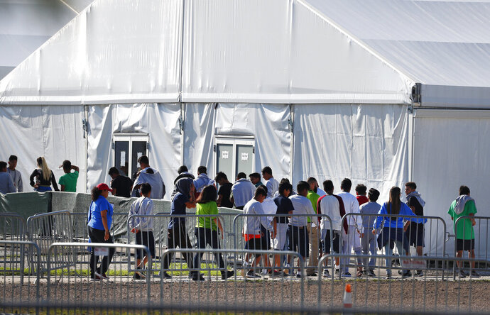 FILE- In this Feb. 19, 2019, file photo, children line up to enter a tent at the Homestead Temporary Shelter for Unaccompanied Children in Homestead, Fla. The U.S. government didn't have the technology needed to properly document and track the thousands of immigrant families separated at the southern border in 2018. That's according to a new report by an internal government watchdog. (AP Photo/Wilfredo Lee, File)