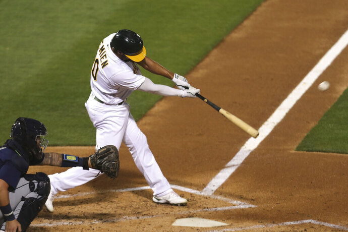 Oakland Athletics' Marcus Semien hits a double against Seattle Mariners during the third inning of a baseball game in Oakland, Calif., Friday, Sept. 25, 2020. (AP Photo/Jed Jacobsohn)