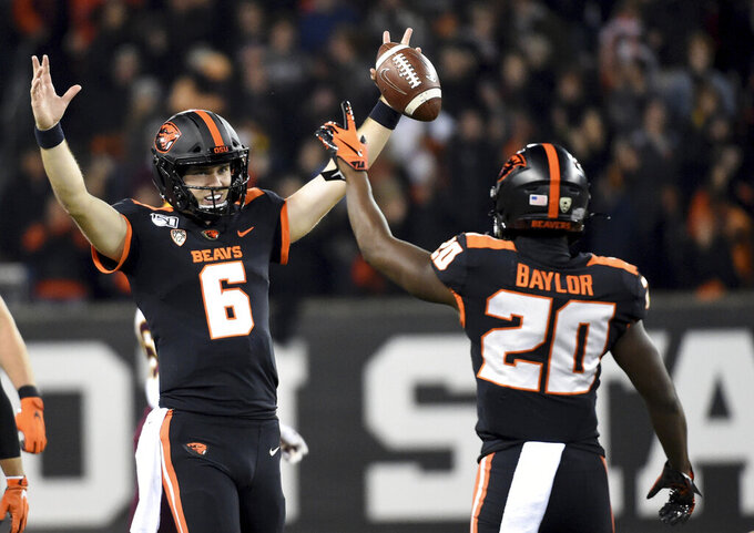 Oregon State quarterback Jake Luton and running back B.J. Baylor celebrate as the clock runs out in an NCAA college football game agains Arizona State in Corvallis, Ore., Saturday, Nov. 16, 2019. (AP Photo/Steve Dykes)