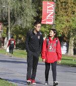Shenlone Wu, 12, and his sister Shenmei, 13, both full-time students at UNLV, walk along a sidewalk at UNLV on Friday, Dec. 6, 2019, in Las Vegas. (Bizuayehu Tesfaye/Las Vegas Review-Journal via AP)