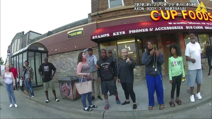 """FILE - This May 25, 2020, file image from a police body camera shows bystanders including Alyssa Funari, left filming, Charles McMillan, center left in light colored shorts, Christopher Martin center in gray, Donald Williams, center in black, Genevieve Hansen, fourth from right filming, Darnella Frazier, third from right filming, as former Minneapolis police officer Derek Chauvin was recorded pressing his knee on George Floyd's neck for several minutes in Minneapolis. To the prosecution, the witnesses who watched Floyd's body go still were regular people -- a firefighter, a mixed martial arts fighter, a high school student and her 9-year-old cousin in a T-shirt emblazoned with the word """"Love."""" (Minneapolis Police Department via AP, File)"""