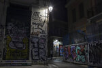 In this Monday, July 22, 2019 photo, a man stands in a street next to a shop and houses covered with graffiti in Athens' Plaka district. Some parts of central Athens are so afflicted with graffiti _ largely undecipherable squiggles in bold, broad strokes _ that few facades remain untouched and property owners give up on repainting. (AP Photo/Petros Giannakouris)