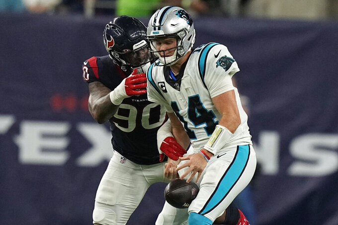 Carolina Panthers quarterback Sam Darnold (14) loses the ball as he is hit by Houston Texans' Ross Blacklock (90) during the first half of an NFL football game Thursday, Sept. 23, 2021, in Houston. (AP Photo/Eric Christian Smith)