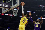 Golden State Warriors' D'Angelo Russell (0) dunks past Los Angeles Lakers' LeBron James (23) during the first half of an NBA basketball game Wednesday, Nov. 13, 2019, in Los Angeles. (AP Photo/Marcio Jose Sanchez)