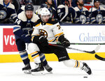 Columbus Blue Jackets defenseman Vladislav Gavrikov, left, of Russia, reaches for the puck next to Boston Bruins forward Jake DeBrusk during the first period of an NHL hockey game in Columbus, Ohio, Tuesday, Jan. 14, 2020. (AP Photo/Paul Vernon)