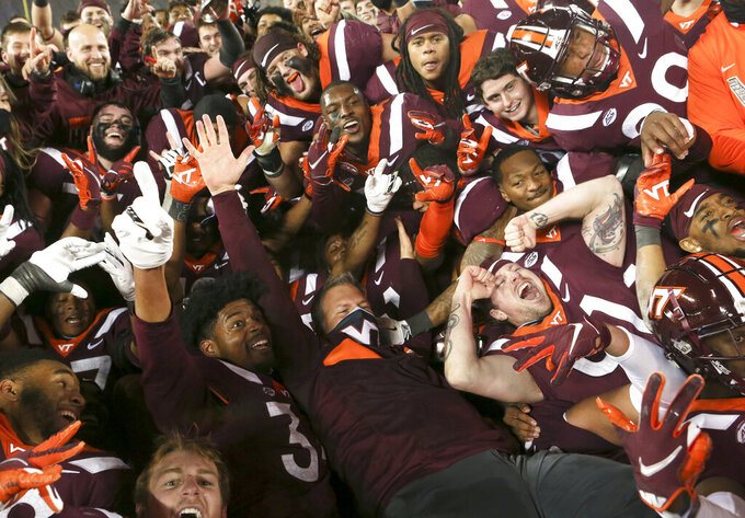 Virginia Tech coach Justin Fuente, center, and his team celebrate a win over Virginia in an NCAA college football game Saturday, Dec. 12, 2020, in Blacksburg, Va. (Matt Gentry/The Roanoke Times via AP, Pool)
