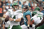 New York Jets quarterback Sam Darnold, left, looks for a receiver as he is pressured by Jacksonville Jaguars defensive tackle Taven Bryan, center, during the first half of an NFL football game, Sunday, Oct. 27, 2019, in Jacksonville, Fla. (AP Photo/Phelan M. Ebenhack)