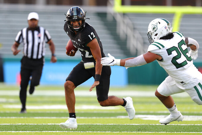 Hawaii quarterback Chevan Cordeiro (12) is flushed from the pocket and runs the ball as Portland State linebacker Nicolas Ah Sam (26) defends during the first half of an NCAA college football game Saturday, Sept. 4, 2021, in Honolulu. (AP Photo/Darryl Oumi)