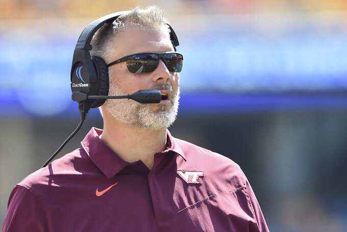 Virginia Tech head coach Justin Fuente looks on during the first half of an NCAA college football game against West Virginia in Morgantown, W.Va., Saturday, Sept. 18, 2021. (AP Photo/William Wotring)