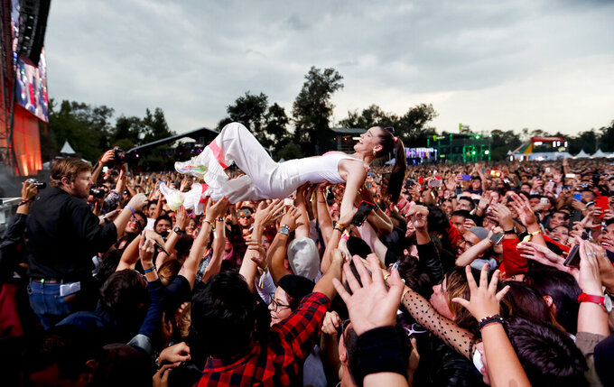 In this Sunday, Nov. 17, 2019 photo, Sophie Hawley-Weld, of German-American musical duo Sofi Tukker, crowd surfs with fans during the Corona Capital music festival in Mexico City. (AP Photo/Eduardo Verdugo)