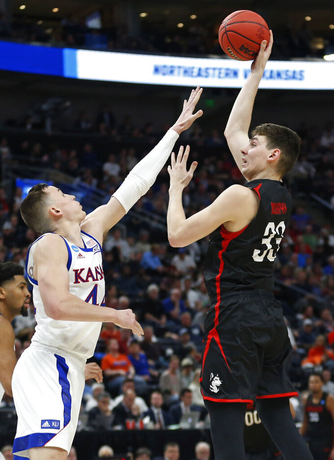 Kansas forward Mitch Lightfoot, left, defends against Northeastern forward Tomas Murphy (33) in the first half during a first round men's college basketball game in the NCAA Tournament, Thursday, March 21, 2019, in Salt Lake City. (AP Photo/Rick Bowmer)