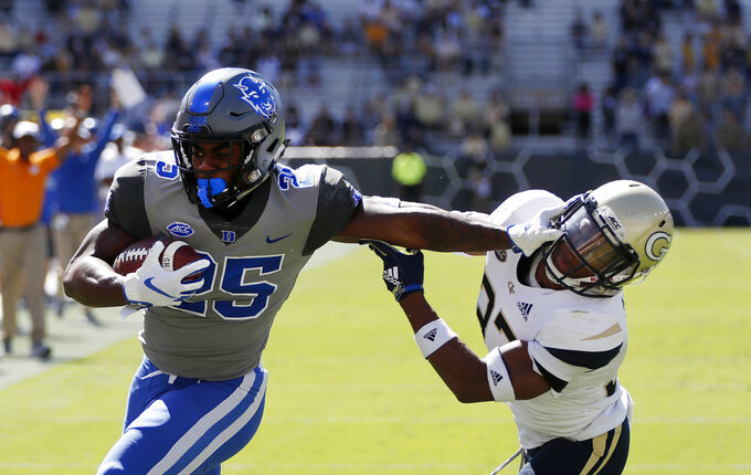 Duke running back Deon Jackson (25) stiff arms Georgia Tech defensive back Jaytlin Askew (33) as he runs for a touchdown during the first half of an NCAA college football game, Saturday, Oct. 13, 2018, in Atlanta. (AP Photo/John Bazemore)