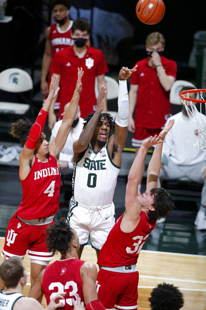 Michigan State's Aaron Henry (0) shoots against Indiana's Khristian Lander (4), Trey Galloway (32), and Trayce Jackson-Davis (23) during the first half of an NCAA college basketball game, Tuesday, March 2, 2021, in East Lansing, Mich. (AP Photo/Al Goldis)