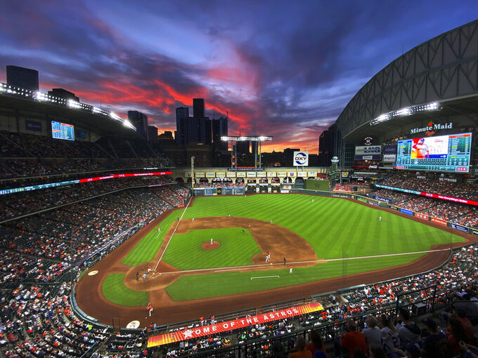 The sun sets behind the downtown Houston skyline during a baseball game between the Houston Astros and the Toronto Blue Jays on Friday, May 7, 2021. (Kevin M. Cox/The Galveston County Daily News via AP)