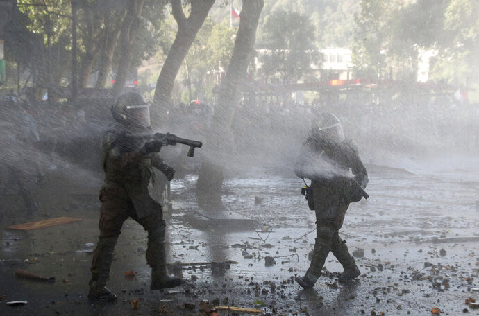 Police are sprayed by their own water cannon during protests in Santiago, Chile, Tuesday, Nov. 19, 2019. Chile has been facing weeks of unrest, triggered by a relatively minor increase in subway fares. The protests have shaken a nation noted for economic stability over the past decades, which has seen steadily declining poverty despite persistent high rates of inequality. (AP Photo/Esteban Felix)