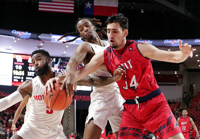 Houston guard Corey Davis Jr. (5) and forward Cedrick Alley Jr., center, battle for a rebound with New Jersey Institute of Technology forward Mohamed Bendary (34) during the first half of an NCAA college basketball game Saturday, Dec. 29, 2018, in Houston. (AP Photo/Michael Wyke)
